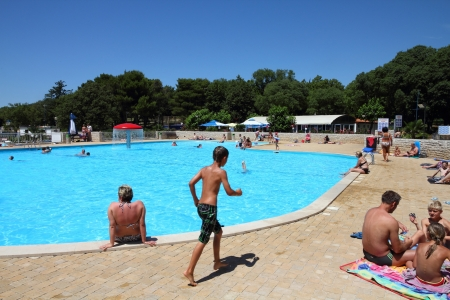 POREC, CROATIA - JUNE 20: Vacationers enjoy a swimming pool at camping site on June 20, 2011 in Porec, Croatia. In 2011 11.2 million tourists visited Croatia, most of them in summer. Stock Photo - 16869634