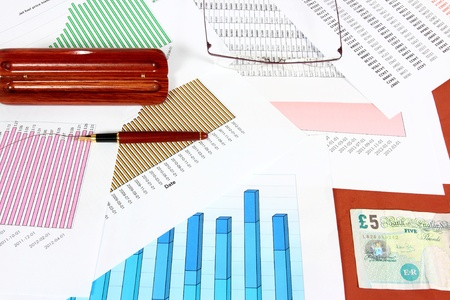 Business objects - fuel price charts, British pounds, ink pen and glasses. Financial concept. photo