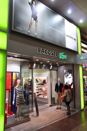 KOBE, JAPAN - APRIL 23: Customer enters Lacoste store on April 23, 2012 in Kobe, Japan. Lacoste is present in 112 countries. It exists since 1933 and has 1,000 stores. Stock Photo - 17863803