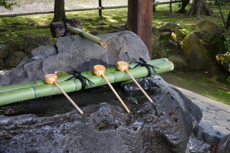 Japan culture - purification fountain with wooden ladles at a Buddhist temple (Ryoanji) in Kyoto.  photo