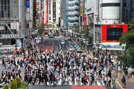 recognized: TOKYO - MAY 11: Commuters hurry on May 11, 2012 in Shibuya, Tokyo. Shibuya crossing is one of busiest places in Tokyo and is recognized thanks to being featured in multiple films.