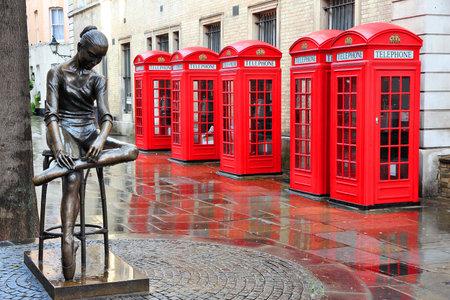 cabina telefonica: Londres, Reino Unido - cajas rojas de tel�fono en tiempo lluvioso mojado. Vista de Broad Court, Covent Garden.