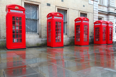 London, United Kingdom - red telephone boxes in wet rainy weather. View of Broad Court, Covent Garden.
