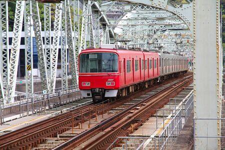 chubu: Inuyama, Japan - town in Aichi prefeture of the region Chubu. Red train crosses railway bridge over Kiso river.