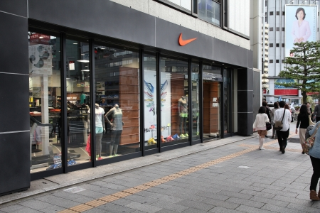 exists: NAGOYA, JAPAN - MAY 3: People walk past Nike store on May 3, 2012 in Nagoya, Japan. Nike is one of most recognized fashion brands. It exists since 1964 and had US$ 19 billion revenue (2010).