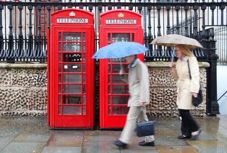London, United Kingdom - red telephone boxes in wet rainy weather. Wet pedestrians with umbrellas.