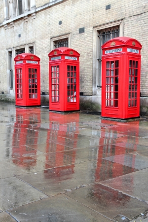 London, United Kingdom - red telephone boxes in wet rainy weather. View of Broad Court, Covent Garden. photo