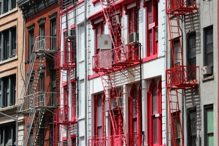 New York City, United States - old residential buildings in Soho district. Colorful fire escape stairs.