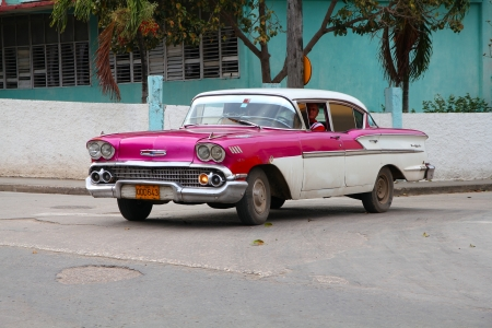 holguin: HOLGUIN, CUBA - FEBRUARY 16: Cuban drives old car on February 16, 2011 in Holguin, Cuba. Recent change in law allows the Cubans to trade cars after it was forbidden for many years.