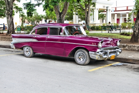 holguin: HOLGUIN, CUBA - FEBRUARY 16: Cubans sit next to an old car on February 16, 2011 in Holguin, Cuba. Recent change in law allows the Cubans to trade cars after it was forbidden for many years.