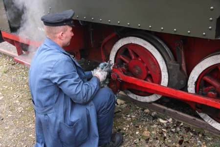 enthusiast: BYTOM, POLAND - SEPTEMBER 22: Enthusiast fixes old narrow gauge steam train on September 22, 2013 in Bytom, Poland. In September 2013 regional narrow gauge celebrated 160th anniversary.