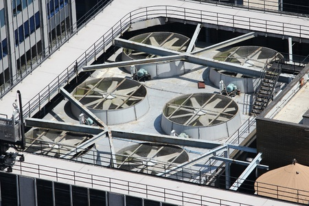 regulating: Exhaust vents of industrial air conditioning and ventilation units. Skyscraper roof top in New York, USA.