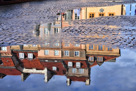 Warsaw, Poland. Old Town rain puddle reflection - tenements at the main square.  Stock Photo