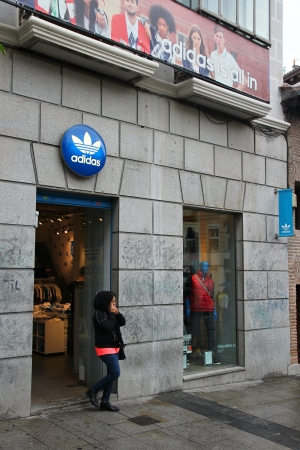 exists: MADRID - OCTOBER 21: Person exits Adidas store on October 21, 2012 in Madrid. Adidas corporation exists since 1924 and had EUR 14.5bn revenue in 2012.