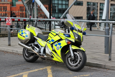 btp: MANCHESTER, UK - APRIL 23: Man walks by Yamaha motorcycle of British Transport Police on April 23, 2013 in Manchester, UK. BTP exists since 1948 and employs 4,290 people.