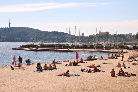 kristiansand: KRISTIANSAND, NORWAY - AUGUST 9: People relax on the beach on August 9, 2010 in Kristiansand, Norway. Kristiansand is the 5th largest municipality in Norway (90 thousand people). Editorial