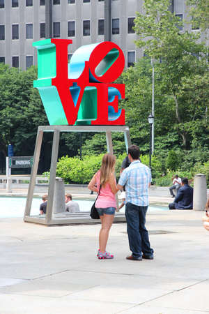 PHILADELPHIA - JUNE 11: People visit Love sculpture on June 11, 2013 in Philadelphia. The famous monument by Robert Indiana is located at JFK Plaza.
