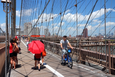 NEW YORK - JULY 5: People walk and cycle along famous Brooklyn Bridge on July 5, 2013 in New York. Almost 19 million people live in New York City metropolitan area.