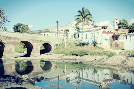 cross processed: Sancti Spiritus, Cuba - cityscape with famous old bridge on the left. River Yayabo. Cross processed vintage color style.