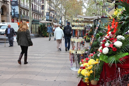BARCELONA, SPAIN - NOVEMBER 6: Tourists walk famous Rambla street on November 6, 2012 in Barcelona, Spain. According to Mastercard, Barcelona is the 15th most visited city worldwide (7.5m in 2012).