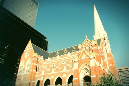 cross processed: Albert Street Uniting Church surrounded by skyscrapers in Brisbane, Queensland, Australia. Cross processed retro color style. Stock Photo
