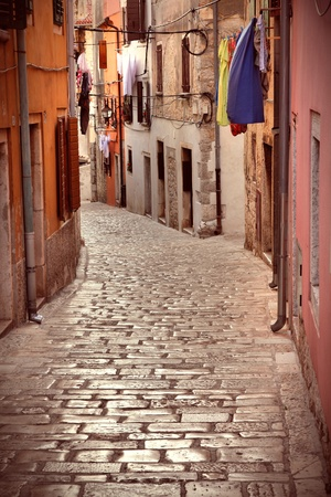 Croatia - Rovinj on Istria peninsula. Old town cobbled street. Cross processing vintage color style. photo