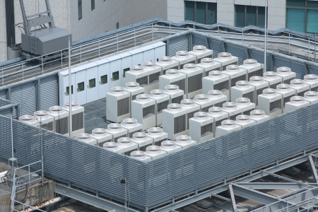 regulating: Exhaust vents of industrial air conditioning and ventilation units. Skyscraper roof top in Kobe, Japan.
