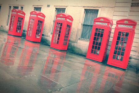 London, United Kingdom - red telephone boxes in wet rainy weather. View of Broad Court, Covent Garden. Cross processed retro style color tone. photo