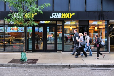 franchises: CHICAGO, USA - JUNE 26, 2013: People walk past Subway sandwich store in Chicago. Subway is one of fastest growing restaurant franchises with 39,747 restaurants in 101 countries.