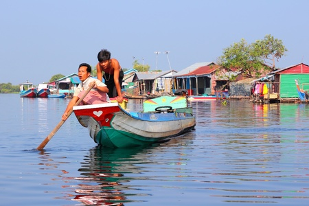 TONLE SAP, CAMBODIA - DECEMBER 11, 2013: Unidentified people ride a boat in floating village on Tonle Sap lake. It is the largest lake in Southeast Asia (up to 16,000 square km).