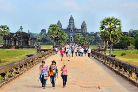 SIEM REAP, CAMBODIA - DECEMBER 9, 2013: Tourists visit Angkor Wat temple complex in Cambodia. The temples are listed as UNESCO World Heritage Site and date back to 12th century.