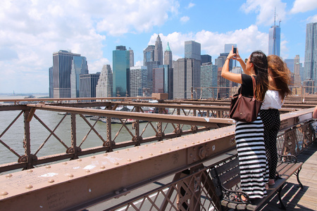 NEW YORK, USA - JULY 5, 2013: Women take photos from Brooklyn Bridge in New York. Almost 19 million people live in New York City metropolitan area.