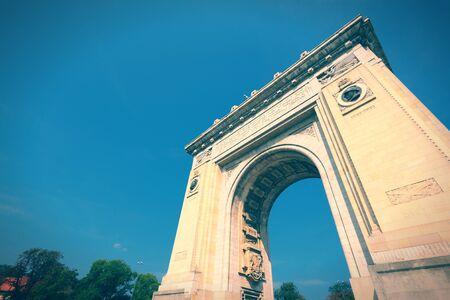 Bucharest, capital city of Romania. Arcul de Triumf - famous triumphal arch. Cross processed color tone - retro style.