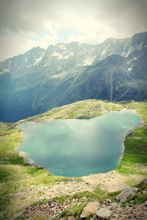 Italy. Negro lake in Stelvio National Park. Route to Gavia Pass in Ortler Alps. Alpine landscape. Cross processing color style - retro tone. photo