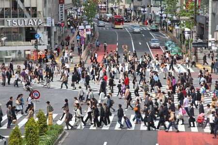 TOKYO, JAPAN - MAY 11, 2012: Commuters hurry in Shibuya, Tokyo. Shibuya crossing is one of busiest places in Tokyo and is recognized thanks to being featured in multiple films.
