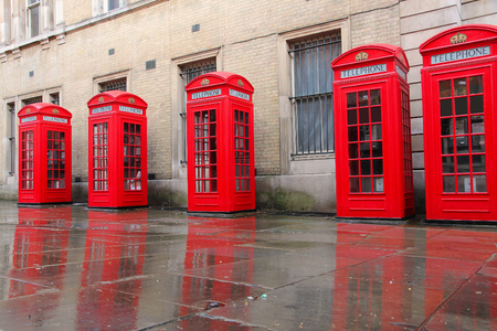 covent: London, United Kingdom - red telephone boxes in wet rainy weather. View of Broad Court, Covent Garden.