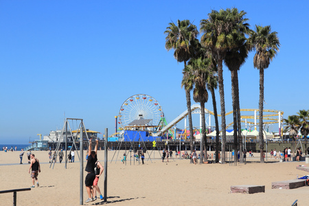 visitors area: SANTA MONICA, UNITED STATES - APRIL 6, 2014: People visit beach in Santa Monica, California. As of 2012 more than 7 million visitors from outside of LA county visited Santa Monica annually.