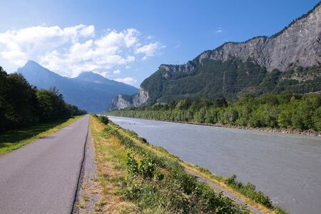 Cycling path along Rhine river in Switzerland. Mountain landscape. photo