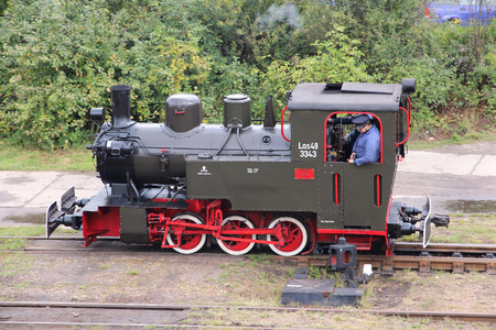 BYTOM, POLAND - SEPTEMBER 21, 2013: Enthusiast rides old narrow gauge steam train in Bytom, Poland. In September 2013 regional narrow gauge celebrated 160th anniversary.