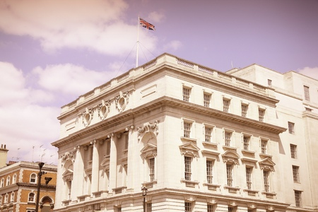 england flag: London, UK - governmental building at Whitehall. British flag. Cross processing color tone - filtered retro style.