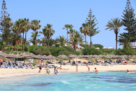 NISSI BEACH, CYPRUS - MAY 16, 2014: People relax at Nissi Beach in Cyprus. Tourism makes about 10 percent of Cyprus budget with 2.4 million annual arrivals (2011).