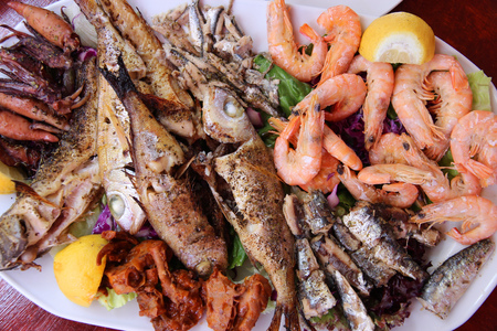 Greek cuisine - traditional grilled seafood plate with shrimps, anchovy, sardines, squid and other fish. photo
