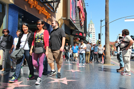 hollywood boulevard: LOS ANGELES, USA - APRIL 5, 2014: People walk famous Walk of Fame in Hollywood. Hollywood Walk of Fame features more than 2,500 stars with inscribed celebrity names.