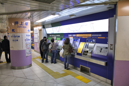 oshiage: TOKYO, JAPAN - APRIL 13, 2012: People buy tickets for Toei Metro in Tokyo. With more than 3.1 billion annual passenger rides, Tokyo subway system is the busiest worldwide.