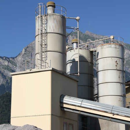 st gallen: Cement factory with Alps in the background. Canton of St. Gallen, Switzerland. Square composition.