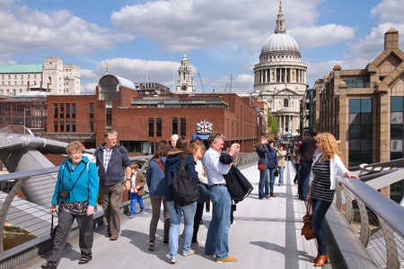 million: LONDON, UK - MAY 13, 2012: People walk the Millennium Bridge in London. With more than 14 million international arrivals in 2009, London is the most visited city in the world (Euromonitor).