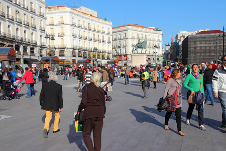 estimated: MADRID, SPAIN - OCTOBER 22, 2012: People visit Puerta del Sol square in Madrid. Madrid is a popular tourism destinations with 3.9 million estimated annual visitors (official data).
