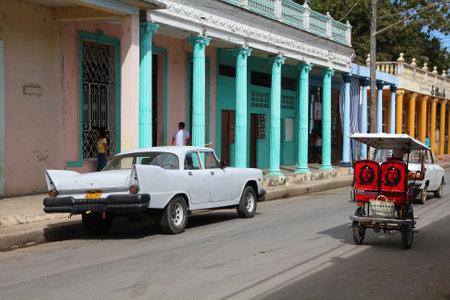 capita: MORON, CUBA - FEBRUARY 19, 2011: People walk past old car in Moron, Cuba. Cuba has one of the lowest car-per-capita rates (38 per 1000 people in 2008). Editorial