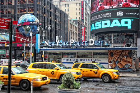 NEW YORK, USA - JUNE 10, 2013: Taxis drive at Times Square in New York. Times Square is one of most recognized landmarks in the world. More than 300,000 people pass through Times Square daily.