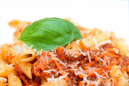 Pasta plate in a restaurant - penne with tomato sauce, minced meat, carrots, parmesan cheese and fresh basil leaf. photo